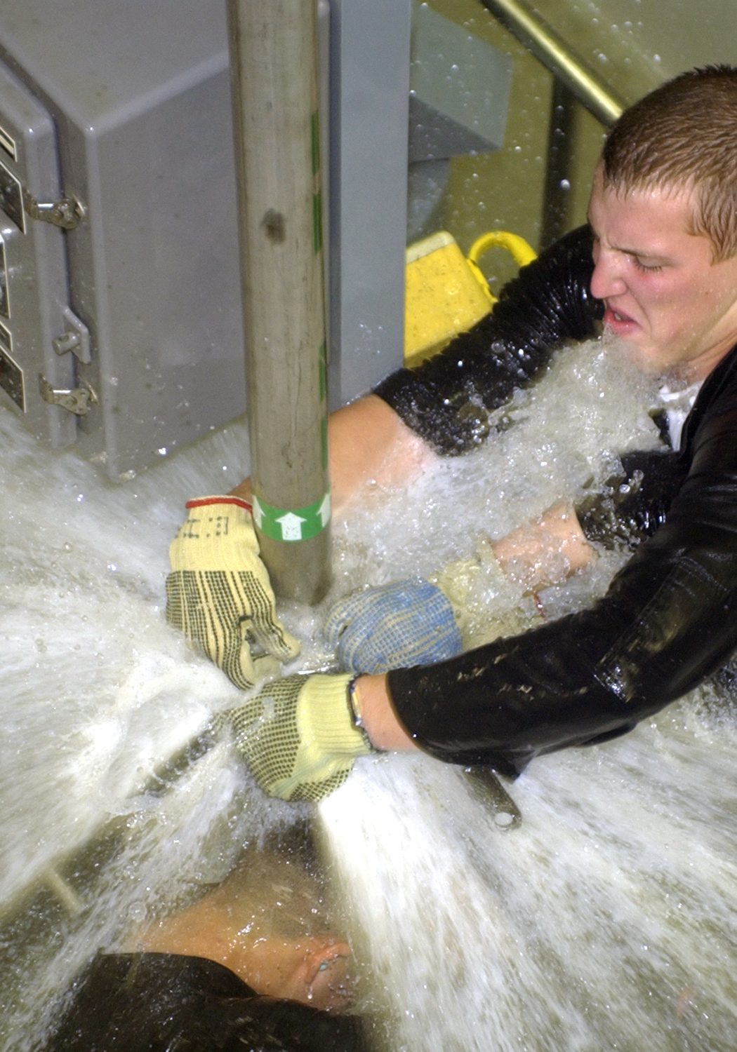 040308-N-0000P-002 Norfolk, Va. (Mar. 8, 2004) Ð Sailors practice repairing leaks in the Òwet trainerÓ on board the Submarine Training Facility (SUBTRAFAC) in Norfolk, Va. The trainer is designed to test the teamwork and damage control capabilities for crews preparing to deploy aboard submarines. Sailors are exposed to leaks from pressurized service pipes within an enclosed space, in effort to provide a controlled yet realistic training environment. U.S. Navy photo. (RELEASED)